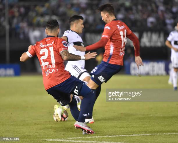Richard Ortiz of Paraguays Olimpia vies for the ball with Rodrigo Rojo and Jonathan Santana of Paraguay's Nacional during their 2017 Copa...