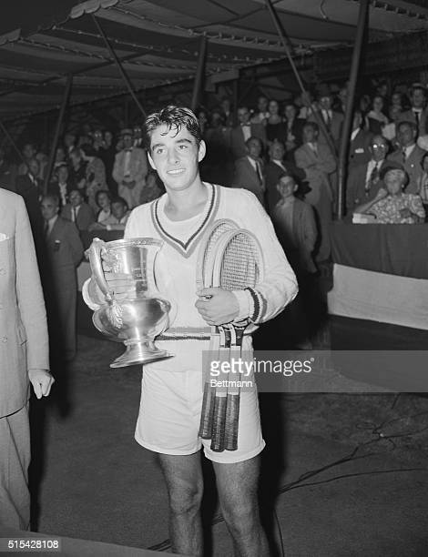 Richard 'Pancho' Gonzales of Los Angeles holds the trophy after he defeated Eric Sturges of South Africa to take the Men's Amateur Tennis Singles...