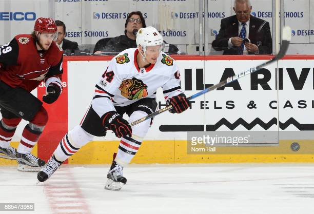 Richard Panik of the Chicago Blackhawks backhands the puck up ice against the Arizona Coyotes at Gila River Arena on October 21 2017 in Glendale...