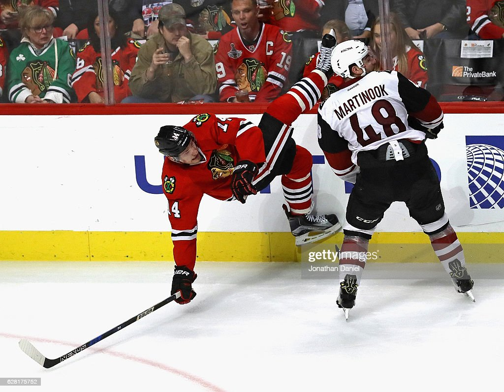 Richard Panik #14 of the Chicago Blackhawks hits the ice after colliding with Jordan Martinook #48 of the Arizona Coyotes at the United Center on December 6, 2016 in Chicago, Illinois. The Blackhawks defeated the Coyotes 4-0.
