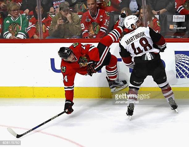 Richard Panik of the Chicago Blackhawks hits the ice after colliding with Jordan Martinook of the Arizona Coyotes at the United Center on December 6...
