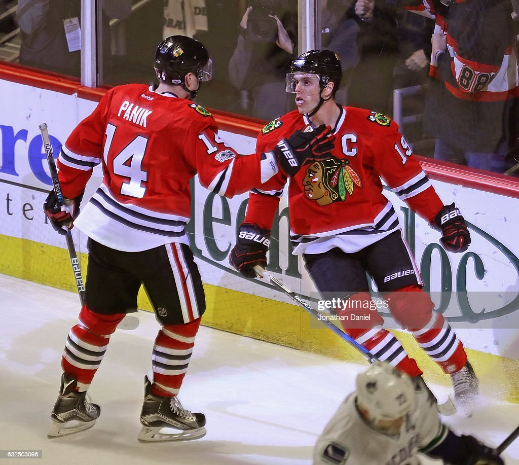 Richard Panik #14 of the Chicago Blackhawks moves to congratulate Jonathan Toews #19 after a third period goal against the Vancouver Canucks at the United Center on January 22, 2017 in Chicago, Illinois. The Blackhawks defeated the Canucks 4-2.
