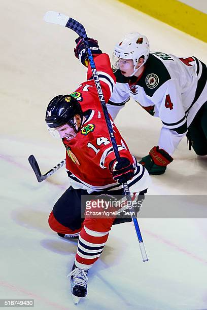 Richard Panik of the Chicago Blackhawks reacts after scoring as Mike Reilly of the Minnesota Wild kneels on the ice behind in the second period of...