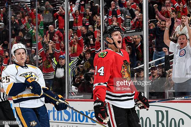 Richard Panik of the Chicago Blackhawks reacts ahead of Matt Carle of the Nashville Predators after scoring the Blackhawks third goal in the first...