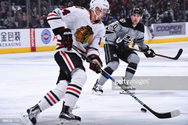 Richard Panik of the Chicago Blackhawks skates with the puck against Tanner Pearson of the Los Angeles Kings during the game on April 8 2017 at...