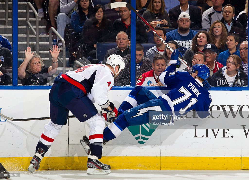 Richard Panik #71 of the Tampa Bay Lightning hits the floor after being hit by John Erskine #4 of the Washington Capitals during the first period of the game at the Tampa Bay Times Forum on February 14, 2013 in Tampa, Florida.