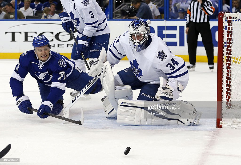 Richard Panik #71 of the Tampa Bay Lightning is hit looking for a rebound in front of goalie James Reimer #34 of the Toronto Maple Leafs at the Tampa Bay Times Forum on April 8, 2014 in Tampa, Florida.