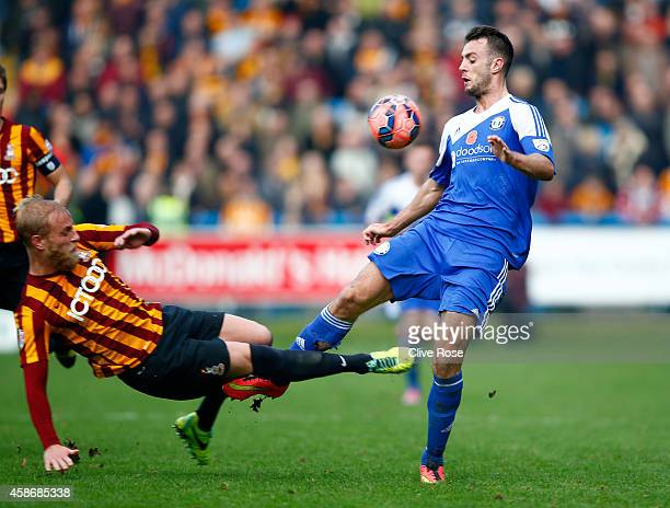 Richard Peniket of Halifax Town is challenged by Andrew Davies of Bradford City during the FA Cup First Round match between FC Halifax and Bradford...
