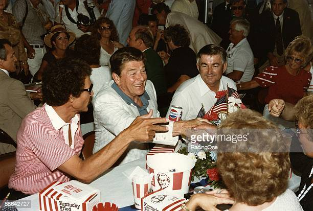 Richard Petty President Ronald Reagan and Bobby Allison enjoy the picnic lunch at the presidential table for the 1984 Firecracker 400 on July 4 1984...
