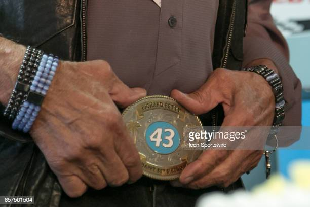 Richard Petty shows off his new specialty belt buckle presented to him as a birthday gift from Auto Club Speedway President Dave Allen during...