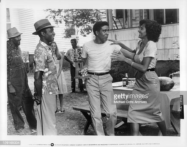 Richard Pryor And Pam Grier laugh and talk with others in a scene from the film 'Greased Lightning' 1977