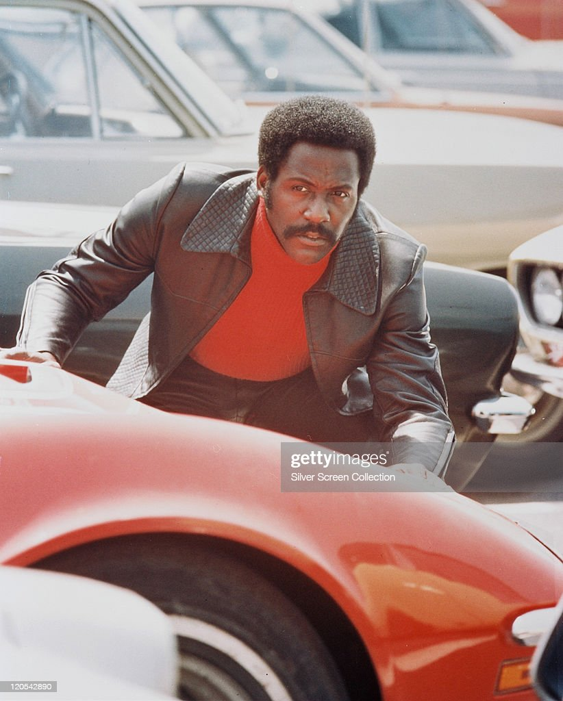 Richard Roundtree US actor crouching behind a red sports car in a publicity still issued for the film 'Shaft' 1971 The blaxploitation film directed...