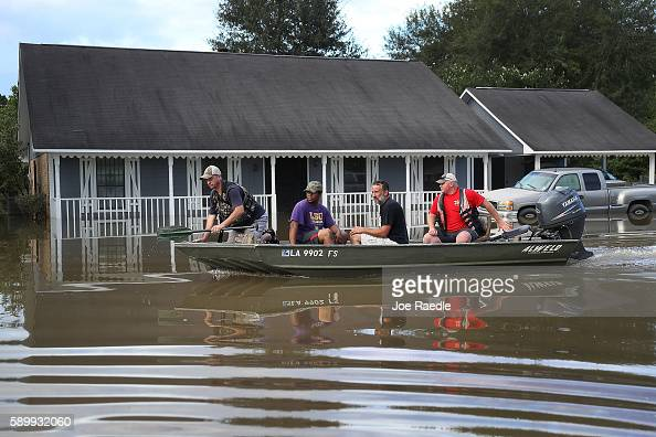 Richard Schafer navigates a boat past a flooded home on August 15 2016 in Baton Rouge Louisiana Recordbreaking rains pelted Louisiana over the...