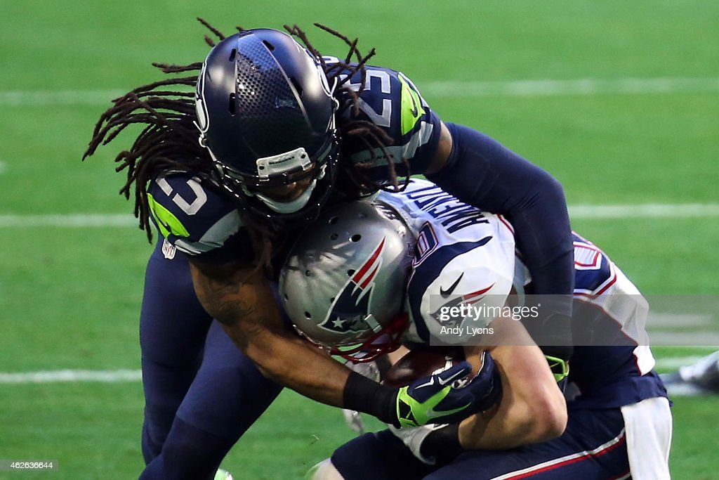 Richard Sherman of the Seattle Seahawks attempts to tackle Danny Amendola of the New England Patriots in the first quarter during Super Bowl XLIX at...
