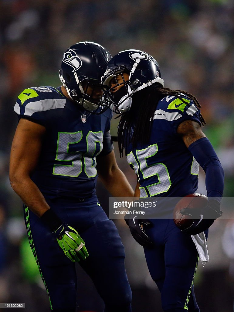 Richard Sherman of the Seattle Seahawks celebrates with KJ Wright after intercepting a ball intended for Philly Brown of the Carolina Panthers thrown...