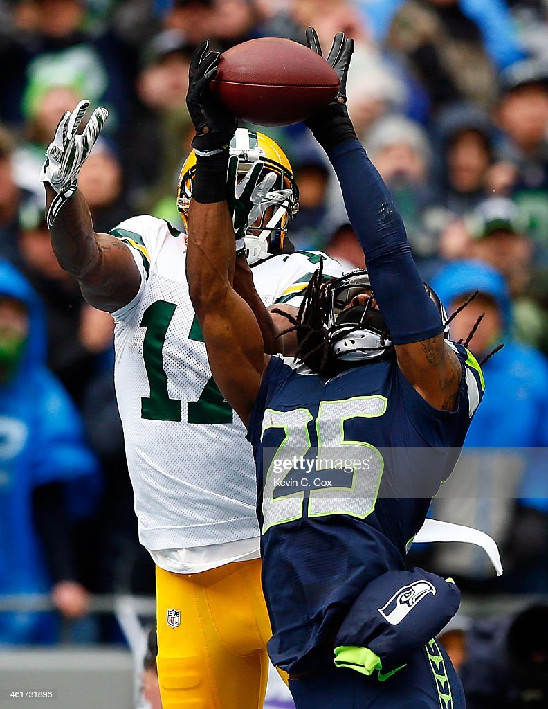 Richard Sherman of the Seattle Seahawks intercepts a pass intended for Davante Adams of the Green Bay Packers in the end zone during the first...