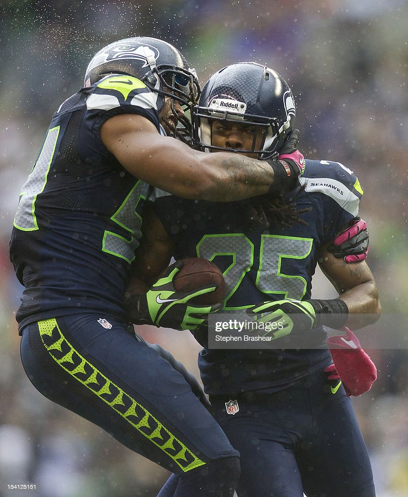 Richard Sherman #25 of the Seattle Seahawks is congratulated by Bobby Wagner #54 after an interception during a game against the New England Patriots at CenturyLink Field on October 14, 2012 in Seattle, Washington. The Seahawks beat the Patriots 24-23.