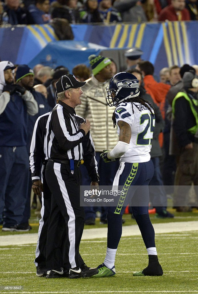 Richard Sherman #25 of the Seattle Seahawks talks with two officials against the Denver Broncos during Super Bowl XLVIII on February 2, 2014 at MetLife Stadium in East Rutherford, New Jersey. The Seahawks won the game 43-8.