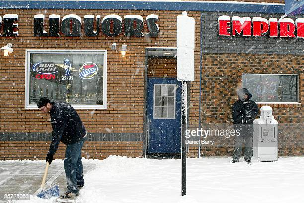 Richard Thelen shovels the sidewalk in front of the Empire Tavern as a heavy snow falls March 302009 in Fargo North Dakota Forecasters were expecting...