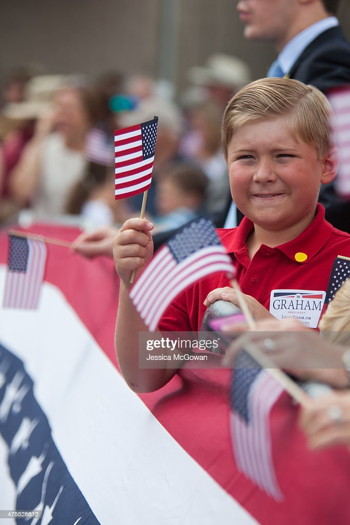 Richard Todd, 9, of Pawley's Island, SC waves flags in support of U.S. Sen. Lindsey Graham (R-SC) as he takes the stage to announce his candidacy for United States President during an outdoor event on June 1, 2015 in Central, South Carolina. Graham is the ninth Republican to join the race for president in 2016.