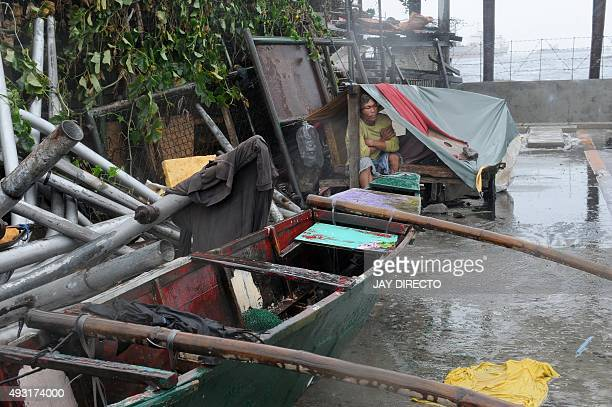 Richard Trinidad 41 a fisherman sits in front of his outrigger boat along the coastal area of Manila Bay on October 18 after the Philippine coast...