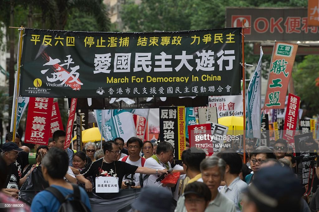 Richard Tsoi (centre L, with white placard), vice chairman of the Hong Kong Alliance in Support of Patriotic Democratic Movements in China, leads demonstrators as they march with banners during a pro-democracy rally ahead of the anniversary of the June 4, 1989 Tiananmen Square crackdown, in Hong Kong on May 29, 2016. People will gather in Hong Kong on June 4 for the annual remembrance ceremony to mark the 27th anniversary of the Tiananmen Square crackdown. / AFP / TENGKU