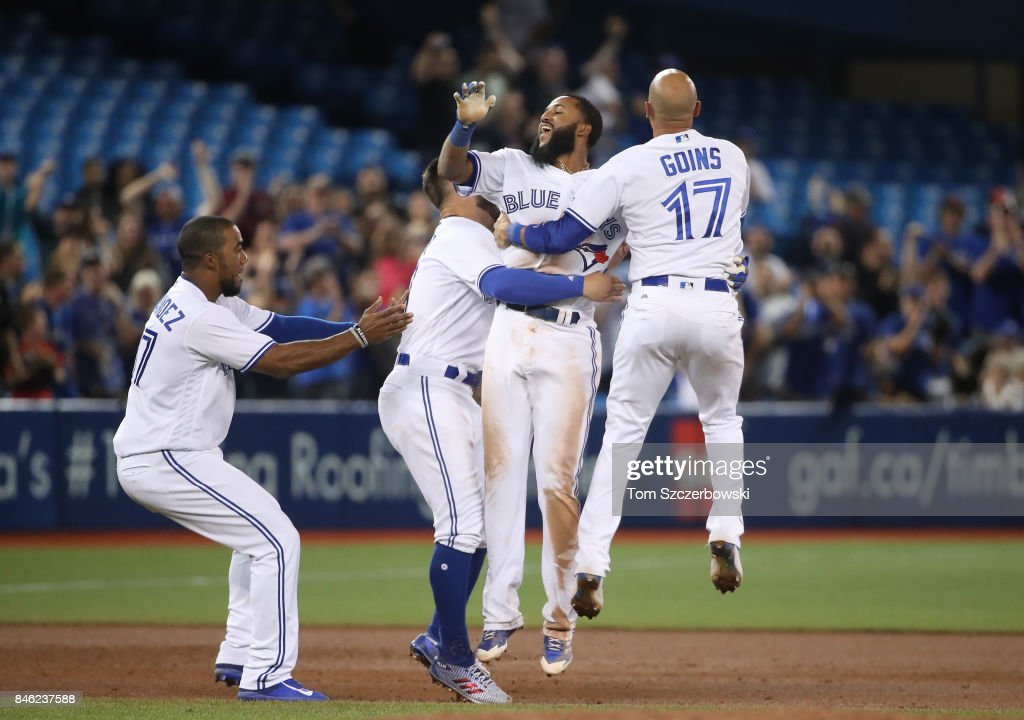 Richard Urena #7 of the Toronto Blue Jays is congratulated by teammates after hitting the game-winning RBI single in the ninth inning during MLB game action against the Baltimore Orioles at Rogers Centre on September 12, 2017 in Toronto, Canada.