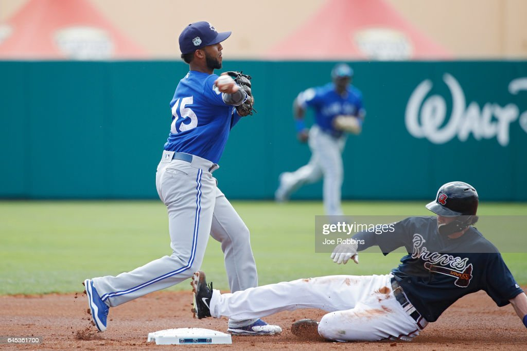 Richard Urena #15 of the Toronto Blue Jays turns a double play against Dansby Swanson #7 of the Atlanta Braves during the spring training game at Champion Stadium on February 25, 2017 in Lake Buena Vista, Florida. The Braves defeated the Blue Jays 7-4.
