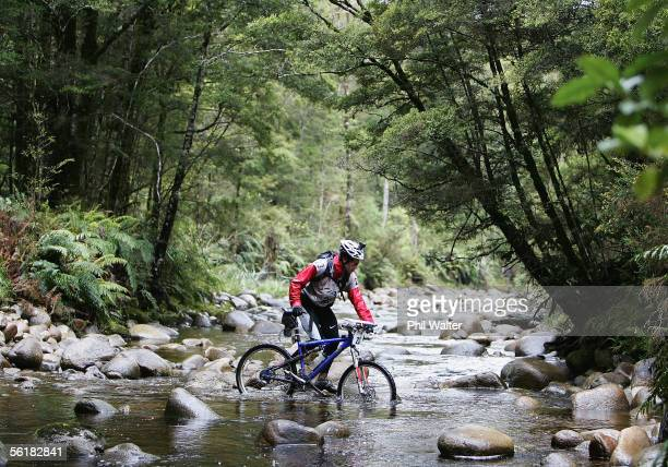 Richard Ussher from the New Zealand team of Balance Vector crosses Goll Creek with her mountain bike on the third day of the Adventure Racing World...