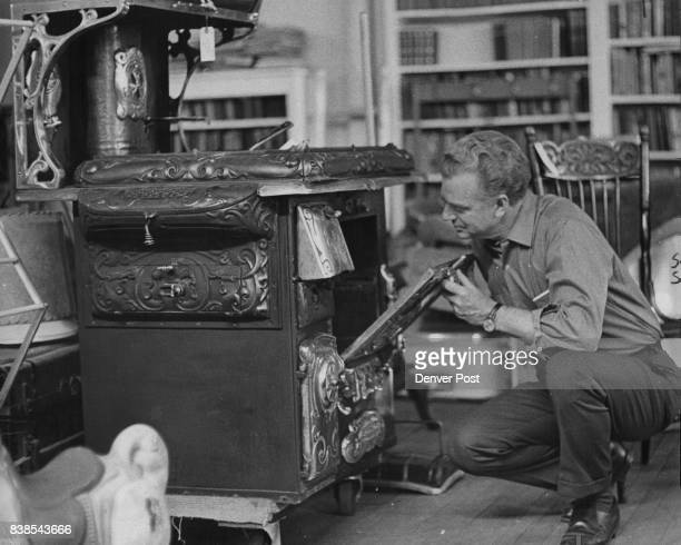 Richard Vaughan proprietor of Richard's Antiques at 600 Ogden St examines an old woodburning cooking stove that is for sale at the St Vincent de Paul...