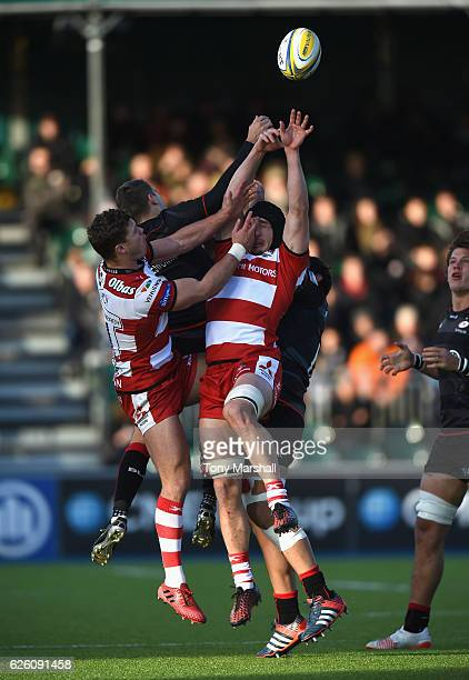 Richard Wigglesworth of Saracens jumps for a high ball with Ben Morgan and Henry Purdy of Gloucester Rugby during the Aviva Premiership match between...