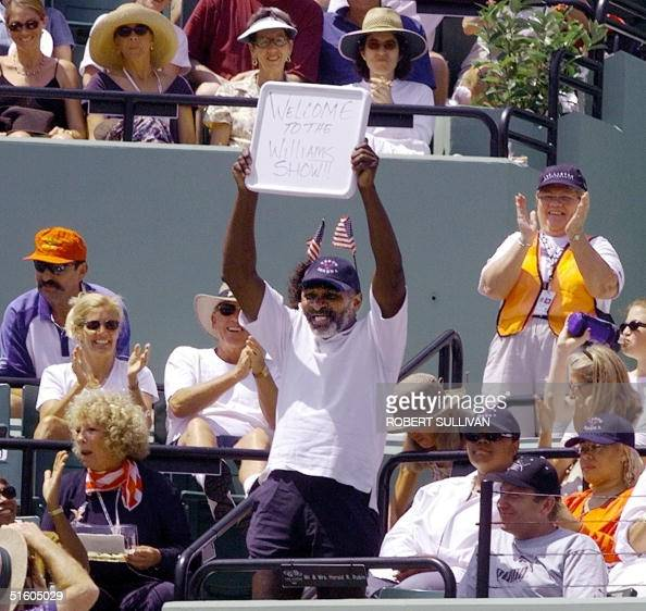 Richard Williams father of Venus and Serena Williams of the US holds up a sign reading 'Welcome to the Williams Show' prior to the start of the...