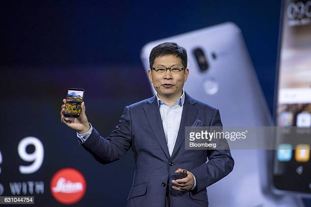Richard Yu chief executive officer of consumer devices division for Huawei Technologies Co holds a new Huawei Mate 9 smartphone as he speaks during a...