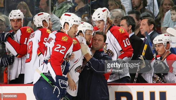 Richard Zednik of the Florida Panthers is tended to by a team trainer and helped by teammate Jassen Cullimore after being cut during the third period...