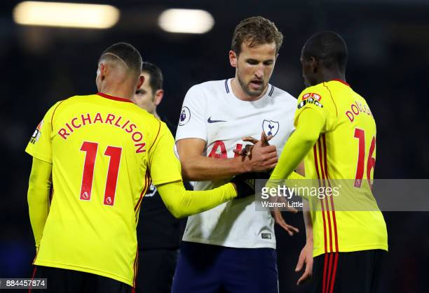 Richarlison de Andrade of Watford and Abdoulaye Doucoure of Watford shake hands with Harry Kane of Tottenham Hotspur after the Premier League match...