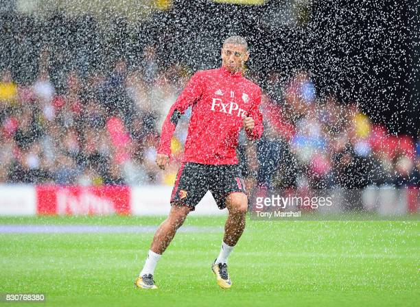 Richarlison of Watford gets caught in the pitch sprinklers during the Premier League match between Watford and Liverpool at Vicarage Road on August...