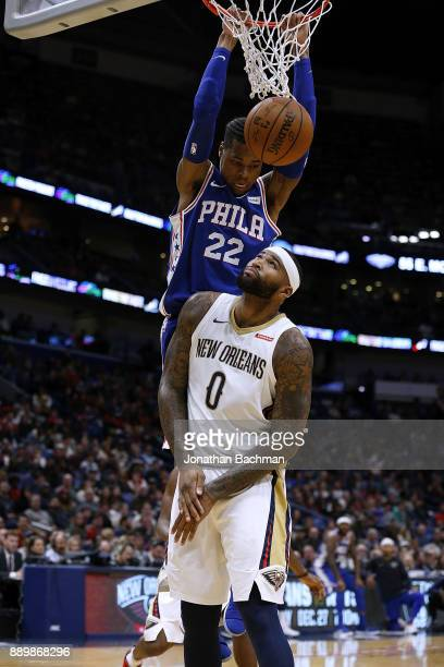 Richaun Holmes of the Philadelphia 76ers dunks over DeMarcus Cousins of the New Orleans Pelicans during the first half of a game at the Smoothie King...