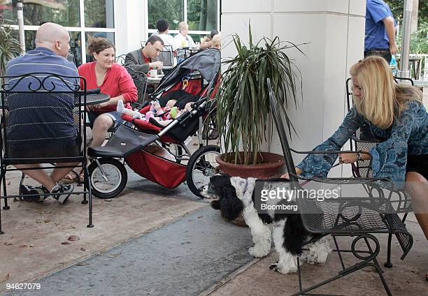 Richelle Hayes right pets her dog Sadie while Nathanael and Fisher with their children Anna Bella and Mia wait for lunch in the patio area of Sam...