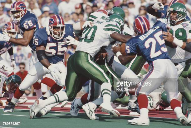 Richie Anderson Full Back for the New York Jets carries the ball as Mark Maddox Linebacker for the Buffalo Bills prepares to tackle during their...