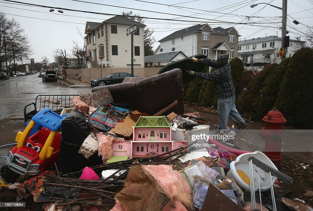 Richie Bain throws household belongings into a garbage pile while helping a friend clean his flood-damaged home on November 7, 2012 in the Staten Island borough of New York City. Residents of the Midland Beach area of Staten Island braced for a Nor'Easter storm that could potentially re-flood areas devastated by Superstorm Sandy.