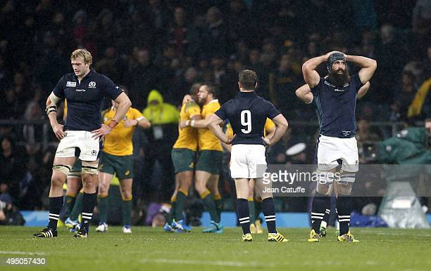 Richie Gray Greig Laidlaw and Josh Strauss of Scotland look dejected while Australian players celebrate the victory following the Rugby World Cup...