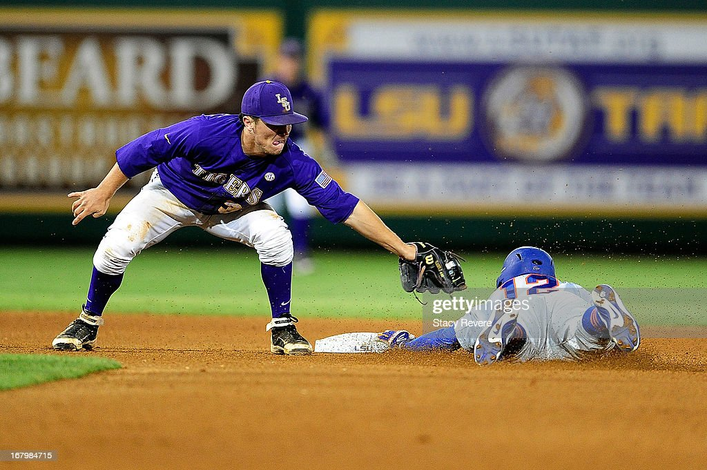 Richie Martin #12 of the Florida Gators dives into second base ahead of the tag by Alex Bregman #30 of the LSU Tigers during a game at Alex Box Stadium on May 3, 2013 in Baton Rouge, Louisiana.