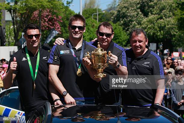 Richie McCaw Dan Carter Steve Hansen and Ian Foster of the All Blacks with the Webb Ellis Cup as they drive towards Hagley Park during the New...