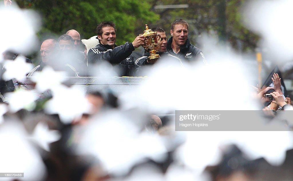 Richie McCaw holds the Webb Ellis Cup while team manager Darren Shand and Brad Thorn look on during the New Zealand All Blacks 2011 IRB Rugby World...