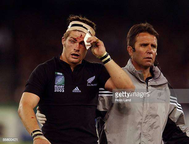 Richie McCaw is escorted from the field for to the blood bin for the second time by team Dr John Mayhew during the All Blacks 299 win over South...