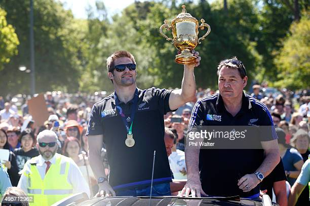 Richie McCaw of the All Blacks and coach Steve Hansen hold the Webb Ellis Cup as they drive through Hagley Park during the New Zealand All Blacks...