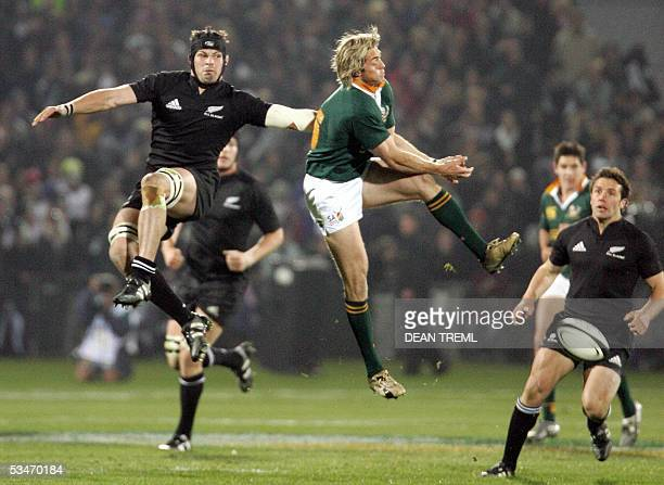 Richie McCaw of the All Blacks and Percy Montgomery of the Springboks jump for a high ball during the Tri Nations rugby union test match between the...