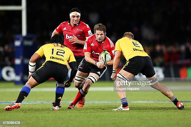 Richie McCaw of the Crusaders runs at Ma'a Nonu and Brad Shields of the Hurricanes during the round 16 Super Rugby match between the Crusaders and...
