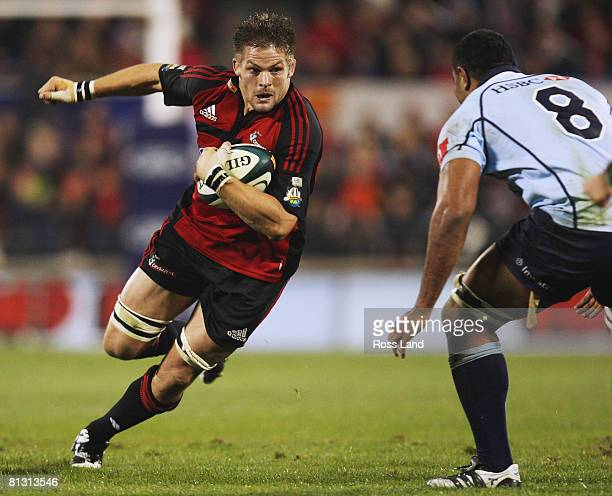 Richie McCaw of the Crusaders runs the ball at Wycliff Palu of the Waratahs during the Super 14 final match between the Crusaders and the New South...