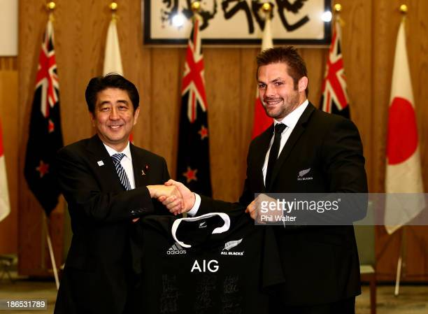 Richie McCaw of the New Zealand All Blacks presents Japanese Prime Minister Shinzo Abe with a signed All Black jersey at the Prime Minister's Office...